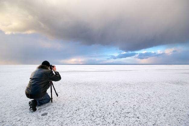 雪原にカメラを持つカメラマン