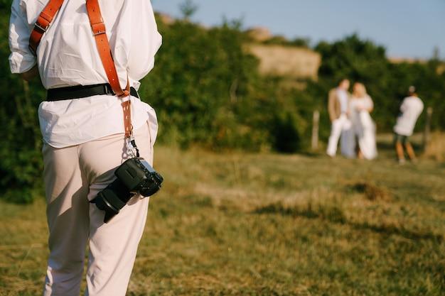 ベルトにカメラを持っている写真家は、新婚夫婦の後ろ姿を数枚撮ります