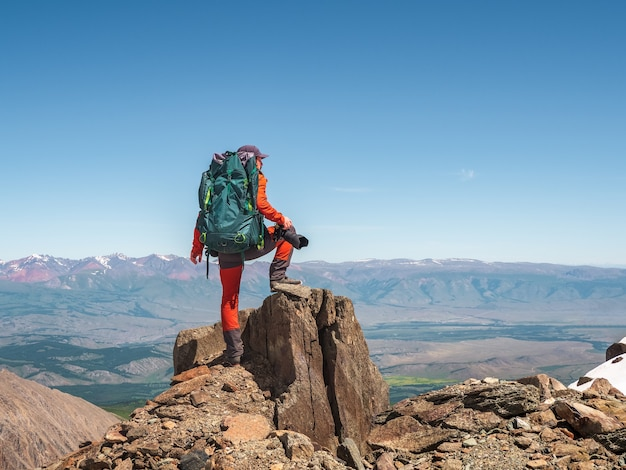 절벽 가장자리에 큰 배낭을 메고 있는 사진작가. 위험한 산과 심연. 푸른 하늘 아래 산계곡의 멋진 전망.