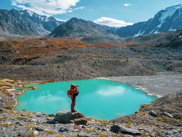 Фотограф с большим рюкзаком на краю обрыва. опасные горы и бездна. потрясающий вид на горную долину под голубым небом.