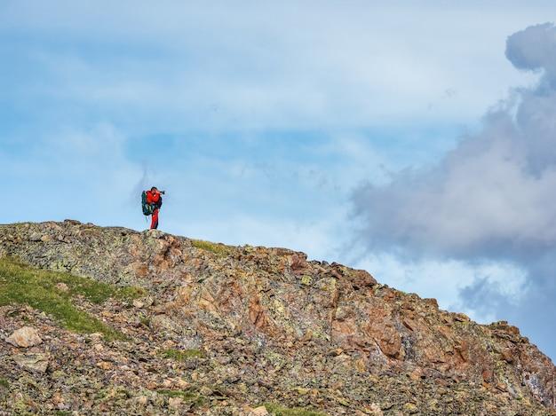 큰 배낭을 메고 푸른 하늘 아래 절벽 가장자리에 있는 아름다운 산 풍경을 사진에 담습니다. 위험한 산과 심연.
