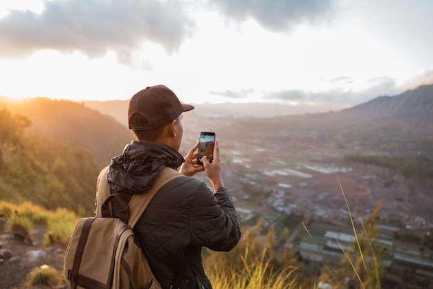 Photographer with backpack and phone taking photo of mountains