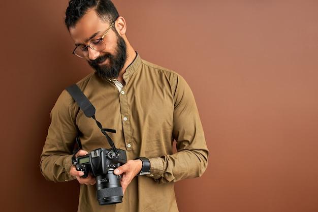 茶色の背景に分離されたカメラを持つ写真家、成功したプロの男性はカメラの画面上の写真を見てください。写真のコンセプト
