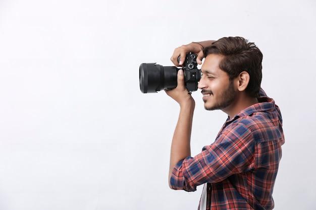 白い壁にカメラを持つ写真家