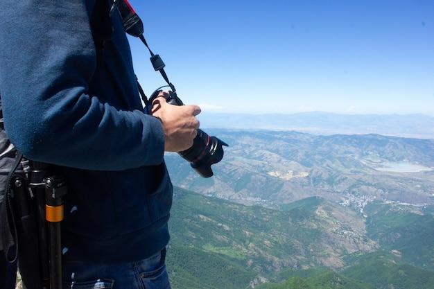 カメラを持った写真家は、青空の下で山の頂上で写真を撮る