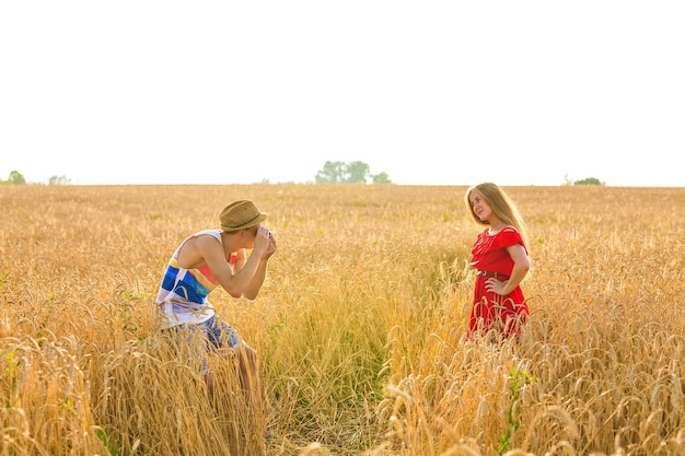 Фотограф с камерой, снимающей молодой красивой женщины в поле.