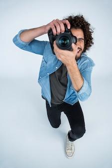 Фотограф с цифровой камерой в студии