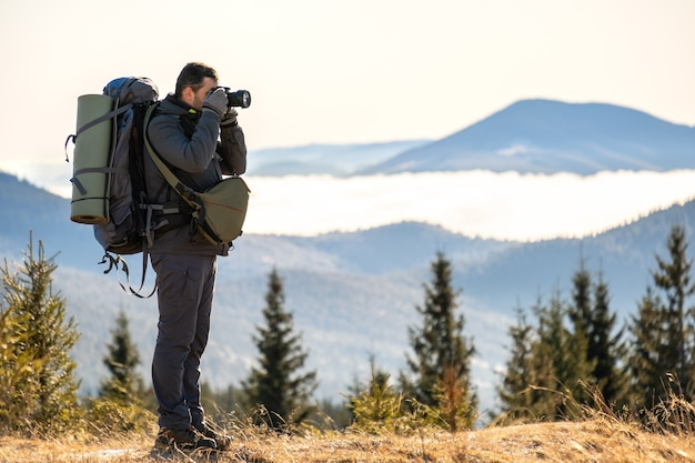Photographer with hiking backpack taking pictures of nature with digital photo camera