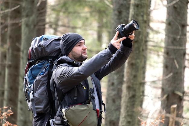 Фотограф с походным рюкзаком фотографирует природу с помощью цифрового фотоаппарата.