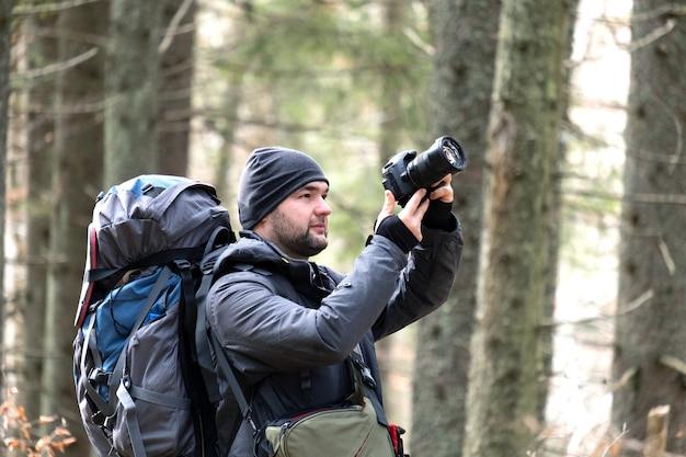 デジタル写真カメラで自然の写真を撮るハイキングバックパックを持つ写真家。