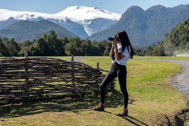 山のあるフィールドで働く長い髪と白いシャツの写真家