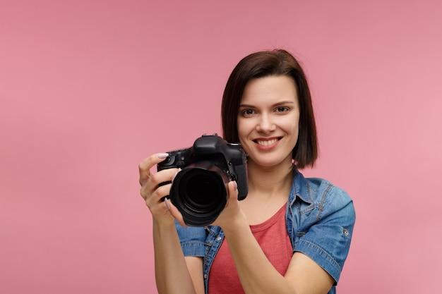 Фотограф с профессиональной камерой, делающей фото в фотостудии