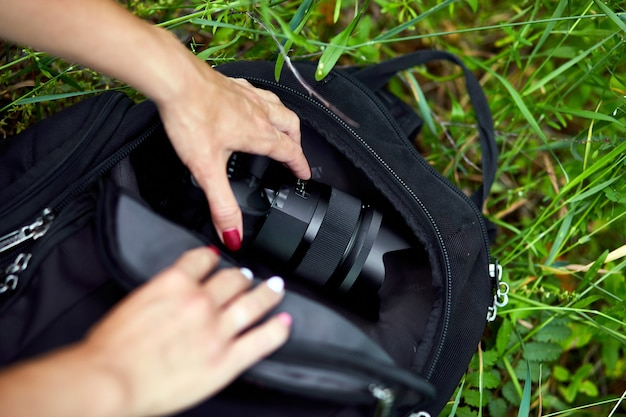Photographer woman pack or takes out her camera backpack, bag appliances for photography top view, outdoor.