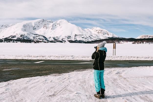 사진 작가 여자는 눈 덮인 산을 촬영합니다. 고품질 사진