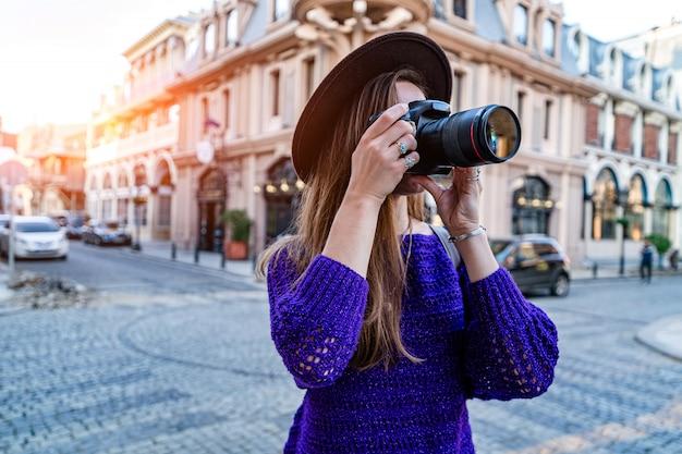Женщина фотографа фотографируя с камерой и объективом dslr во время гулять вокруг европейского города