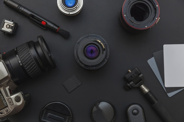 Photographer work place with dslr camera system and camera accessory on dark black background