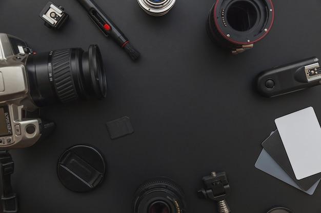 Dslr 카메라 시스템, 카메라 청소 키트, 렌즈 및 카메라 액세서리가 어두운 검정색 배경에있는 사진 작가 작업장