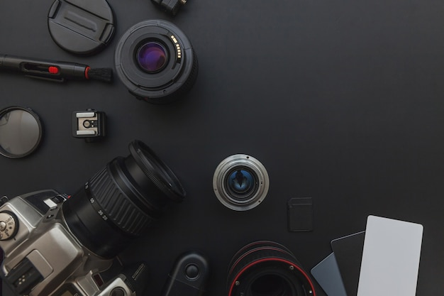 Photographer work place with dslr camera system, camera cleaning kit, lens and camera accessory on dark black background