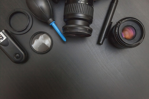 Photographer work place with dslr camera system, camera cleaning kit, lens and camera accessory on dark black table background