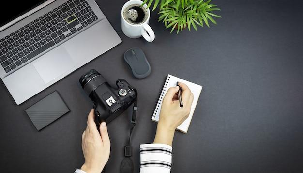 집에서 일하는 사진 작가 집에서 일하는 여성의 손에 커피 한 잔