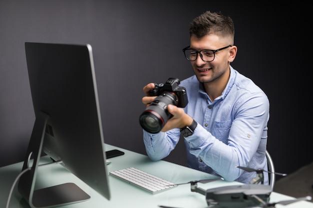オフィスのデスクトップコンピューターで作業するカメラマン