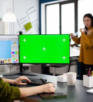 Фотограф работает над зеленым макетом экрана, компьютером с цветным ключом, изолированным дисплеем, сидя за столом, ретушируя женский портрет в программе для редактирования фотографий