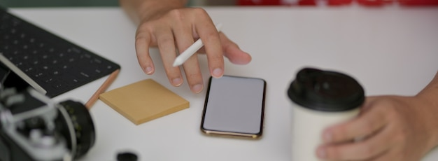 白い作業台にモックアップのスマートフォンで作業する写真家