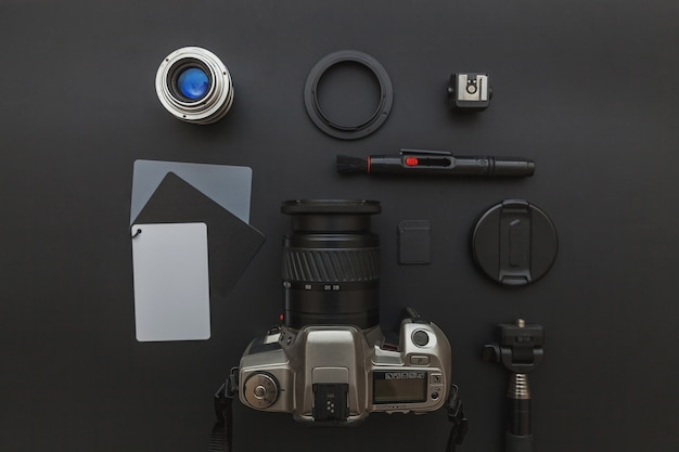 Dslr 카메라 시스템, 카메라 청소 키트, 렌즈 및 카메라 액세서리가 어두운 검정색 배경에있는 사진 작가 직장