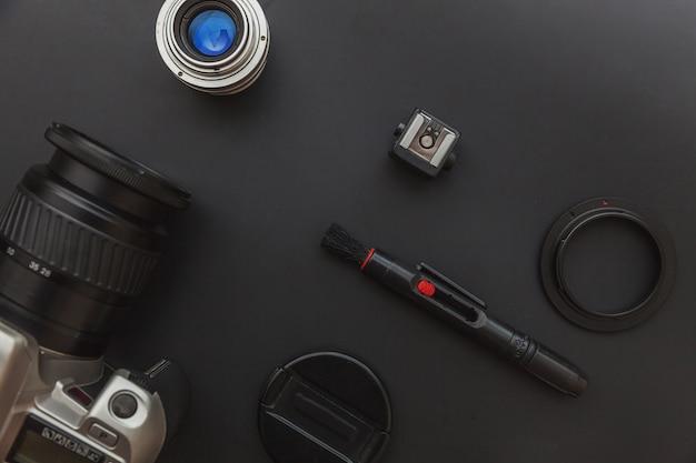 Рабочее место фотографа с системой камеры dslr, комплектом чистки камеры, объективом и аксессуаром камеры на темном черном фоне стола. хобби путешествия фотография концепции. плоская планировка сверху.
