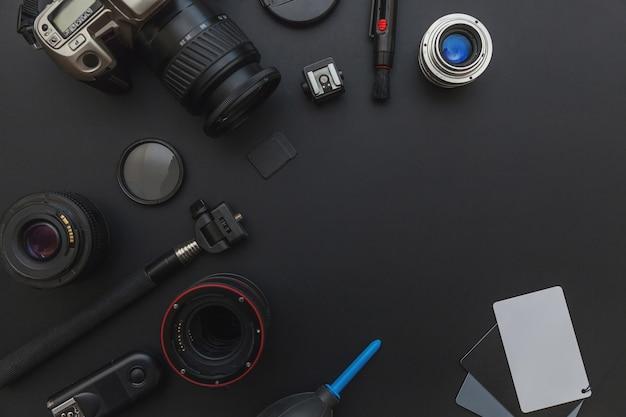Dslr 카메라 시스템, 카메라 청소 키트, 렌즈 및 카메라 액세서리가 어두운 검은 색 테이블 배경에있는 사진 작가 직장.