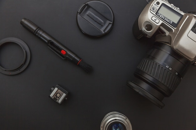Photographer workplace with dslr camera system, camera cleaning kit, lens and camera accessory on dark black background
