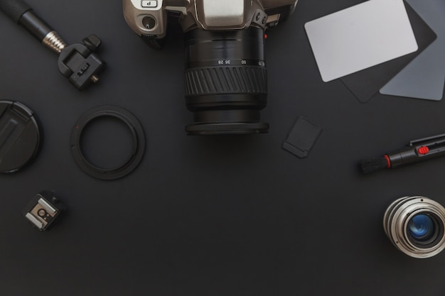 Photographer workplace with dslr camera system, camera cleaning kit, lens and camera accessory on dark black table background. hobby travel photography concept. flat lay top view copy space.