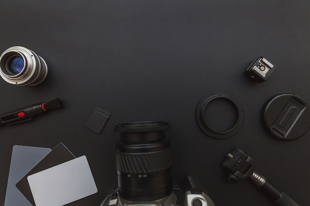 Photographer workplace with dslr camera system, camera cleaning kit, lens and camera accessory on dark black table. hobby travel photography concept. flat lay top view copy space.