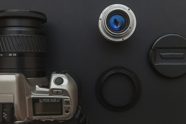 Photographer workplace with dslr camera system and lens on dark black table background. hobby travel photography concept. flat lay top view copy space.