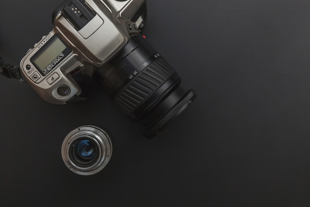 Photographer workplace with dslr camera system and lens on dark black table background