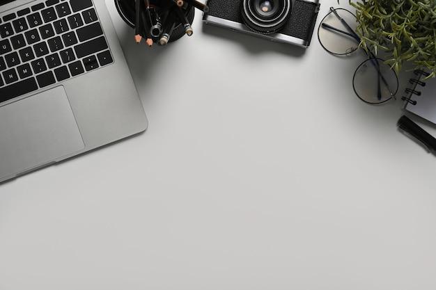 白いテーブルの上にラップトップコンピューター、カメラ、観葉植物と写真家のワークスペース。