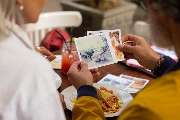 사진 예술. 점심 시간에 카페에서 아내와 함께 앉아 찍은 사진을 바라보는 집중된 남자.