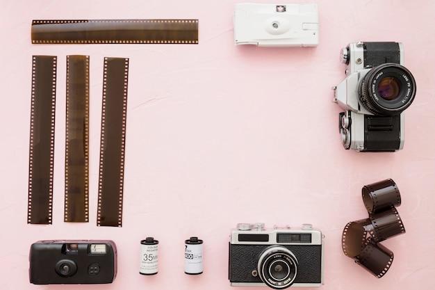 분홍색 배경에 사진 필름 및 카메라