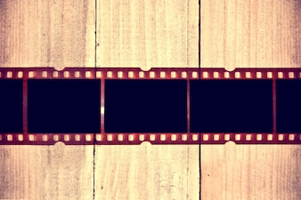 Photographic film on wooden background.
