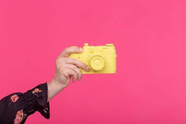 写真とヴィンテージのコンセプト-ピンクの壁に黄色のレトロなカメラと女性の手