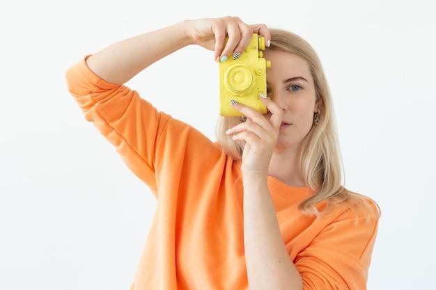 Фотографирование, эмоции и винтажная концепция - удивленная девушка с ретро-камерой над белой