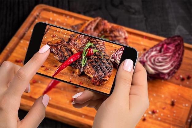 食べ物のコンセプトを撮影する-観光客はスマートフォンで木の板を切ってすぐに食べられるビーフステーキ料理の写真を撮ります。レストランでのオリジナル料理