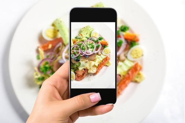 음식 개념을 사진에 담는 여성은 하얀 접시에 양상추, 계란, 토마토, 양파 링, 고추를 넣은 신선한 샐러드 사진을 찍습니다. 평면도. 확대
