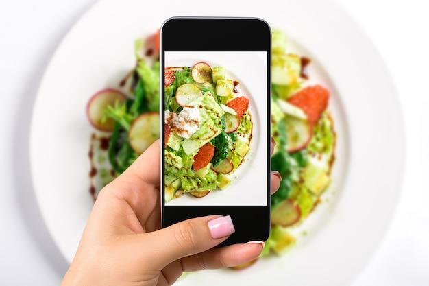 음식 개념을 사진에 담는 여성은 하얀 접시에 상추, 무, 자몽, 치즈, 감귤류 드레싱을 곁들인 신선한 샐러드 사진을 찍습니다. 상위 뷰 클로즈업