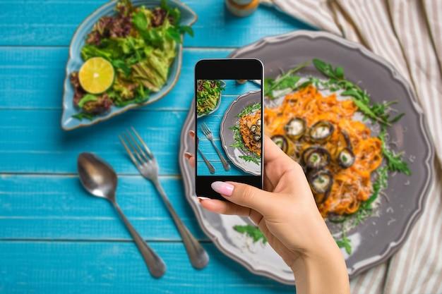 Фотографирование концепции еды женщина фотографирует пасту с баклажанами, помидорами, сыром, рукколой и салатом