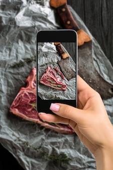 Фотографирование концепции еды - женщина фотографирует сырые, сухие выдержанные стейки на косточке для гриля со свежими травами и тесаком. вид сверху