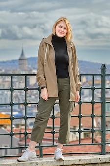 Фотографируя для социальных сетей на фоне городского пейзажа стамбула, молодая белая женщина гуляет по городу зимой.