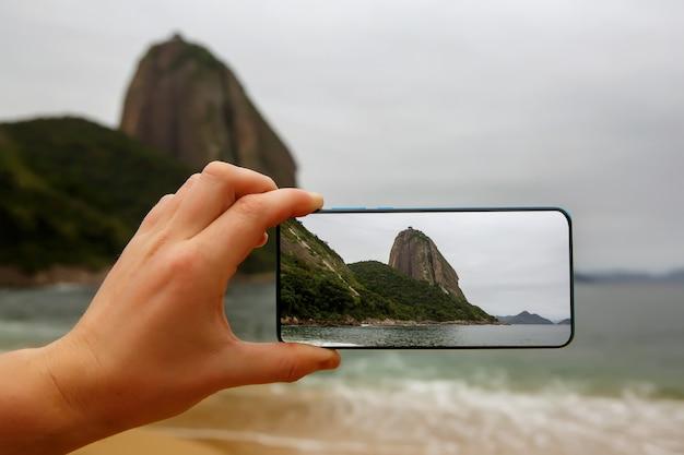 Photographing a sugar loaf mountain on a smartphone, rio-de-janeiro