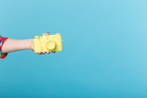 Photographing and vintage concept - female hand with yellow retro camera on blue wall with copy space