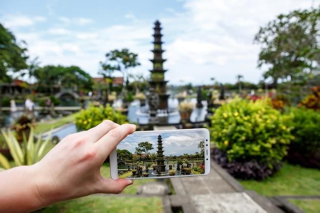 スマートフォンを手にした写真。旅行のコンセプト。バリ島のティルタガンガの水の宮殿。